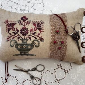 a sweing pillow with flower motifs in burgundy