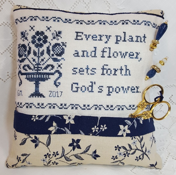 pillow in blue with sentence on God flowers and plants embroidered