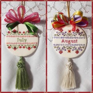 two christmas ornaments embroidered with bow and tassle for months of July and August