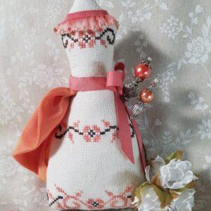 a coral pincushion shaped like a dress