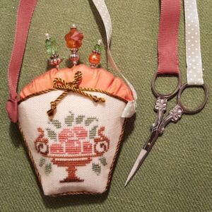 a sewing accessory with a basket pincushion and bone rings looped ribbon handles for scissors