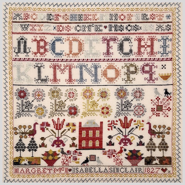 sampler with alphabet and flowers and a house
