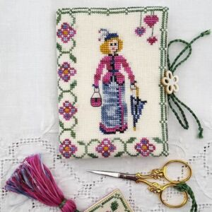 little embroidered sewing set of a woman holding an umbrella in victorian clothing with needlebook and scissor fob