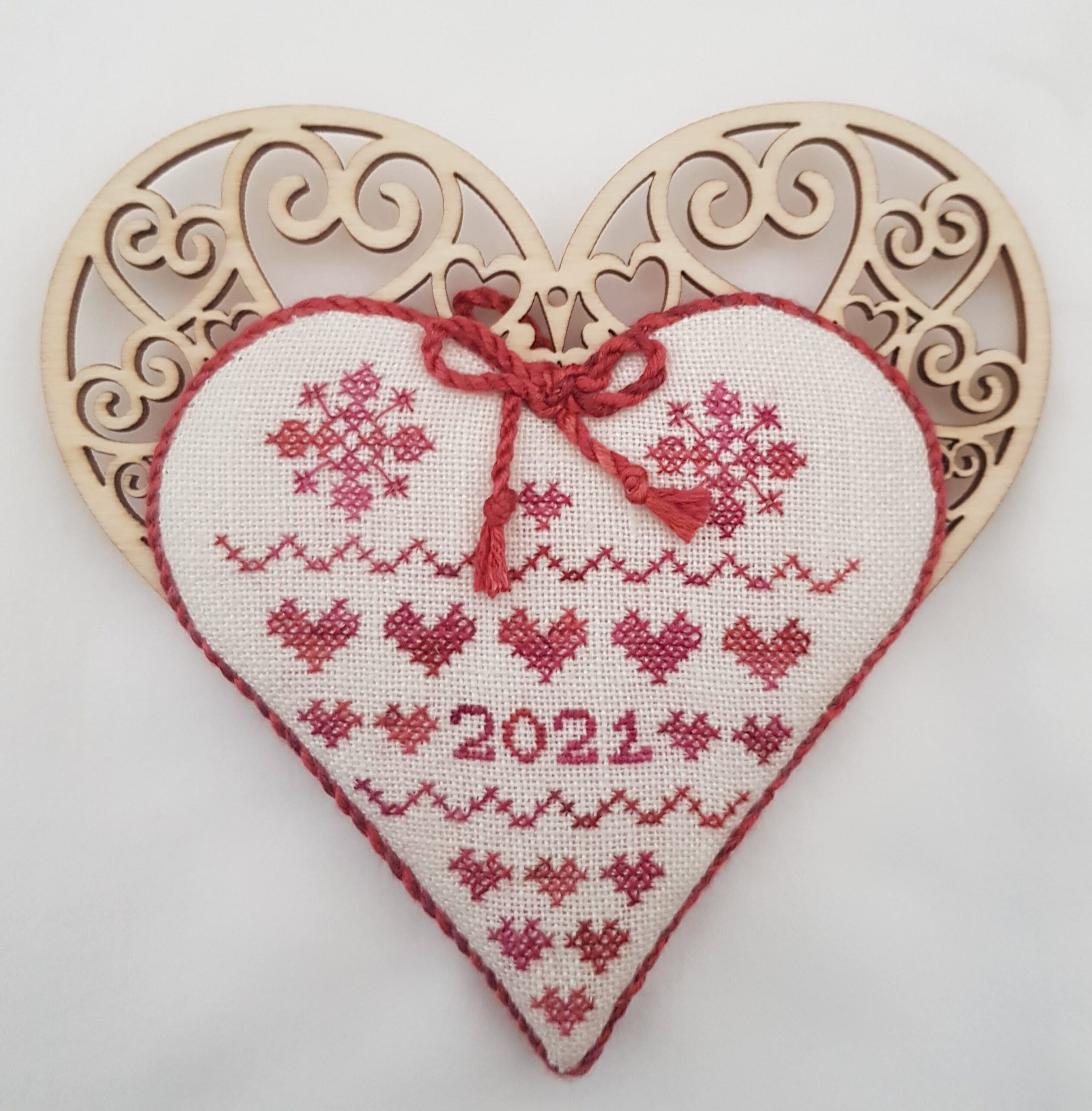 one side wooden heart with stitched red hearts and flowers